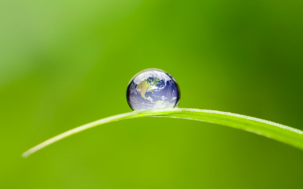 Earth in water droplet on green background